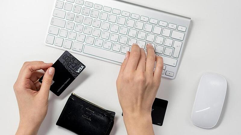 Woman typing at a keyboard with a credit card in hand.