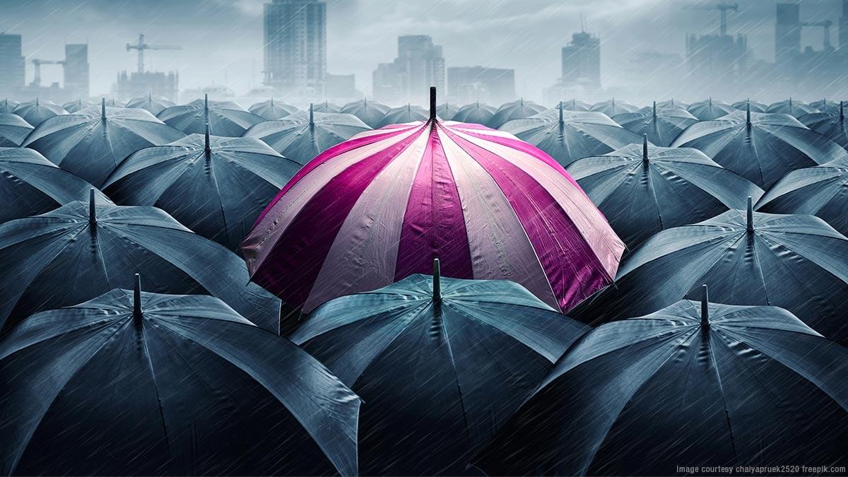 One pink umbrella in a croud of grey umbrellas